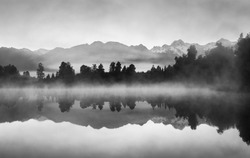 Beautiful reflections of Southern Alps at Lake Matheson, New Zealand, in the early morning mist, in black and white.