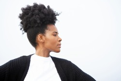 Beautiful, regal, young black woman stands powerfully with her arms outstretched, wearing a white shirt, black sweater, and an updo hairstyle, looking right against sky