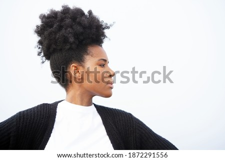 Beautiful, regal, young black woman stands powerfully with her arms outstretched, wearing a white shirt, black sweater, and an updo hairstyle, looking right against sky                                ストックフォト ©