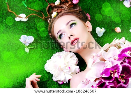 Beautiful relaxed woman lying on a grass surrounded by flowers. Beauty of spring and summer.