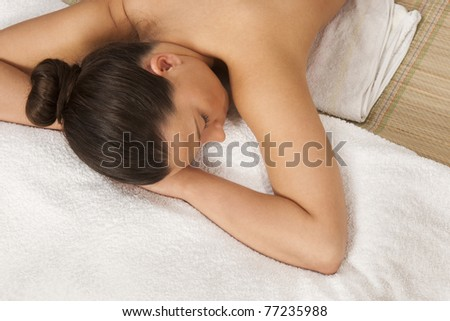 beautiful relaxed woman lying on a massage table in spa center