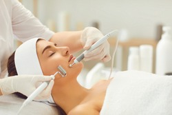 Beautiful relaxed woman receiving apparatus facial microcurrent treatment from therapist in beauty wellness salon, side view. Electrical impulses in cosmetology concept