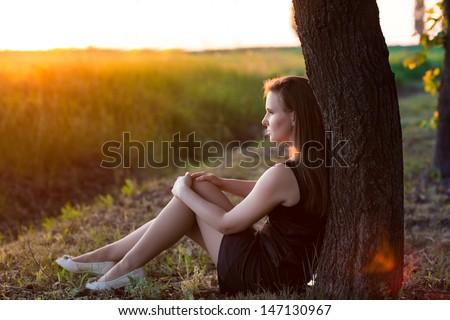 Beautiful relaxed woman sitting near the tree enjoying sunset
