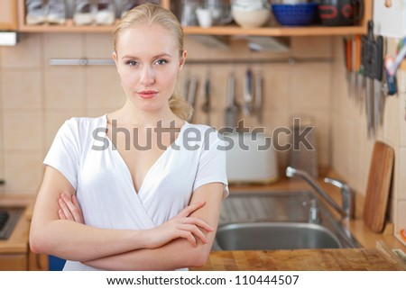 Beautiful relaxed woman standing at the kitchen counter ready to cook a stunning dish