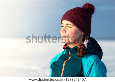 Beautiful relaxed young woman enjoying cold sunny winter weather, smiling, relaxing outdoors with her eyes closed, breath deeply fresh air. ストックフォト ©