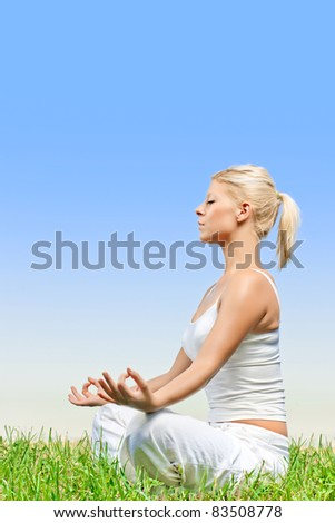 Beautiful relaxed young woman meditating outdoors.