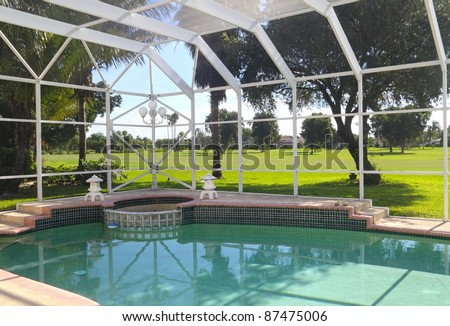 Beautiful residential screened-in swimming pool with patio and patio furniture.