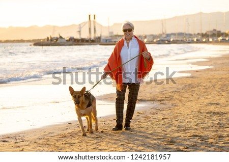 Beautiful retired older woman and pet german shepard dog walking along the shore sea ocean on beach in Companionship Benefits of animals Keeping active Retirement lifestyle and Dog friendly tourism.