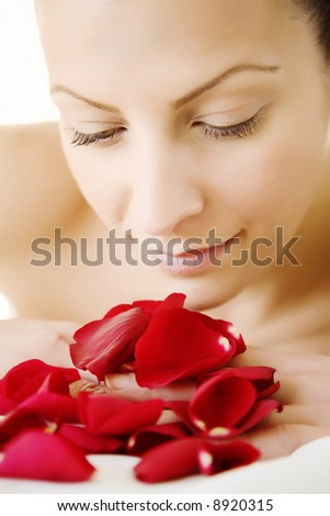 beautiful retouched woman enjoying a bunch of rose-petals