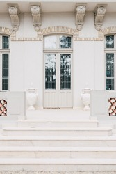 Beautiful retro entrance to a classical style building with white walls, front door stairs and vintage glass windows. Symmetrical architectural detail. Wedding venue or arts gallery museum.