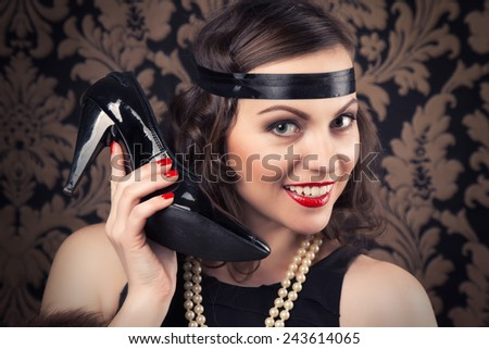 beautiful retro woman holding a black shoe like phone receiver against vintage wallpapers