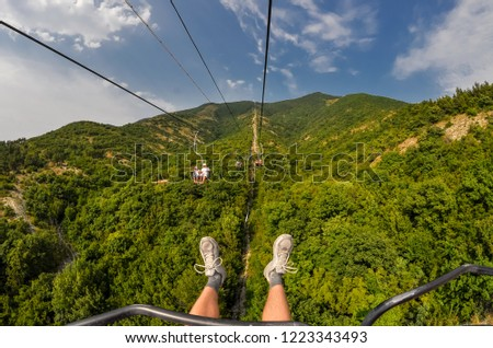 Beautiful rich landscape on the cable car. On the mountain there are many green trees against the blue sky. Photographer's feet over the precipice and green forest. #1223343493