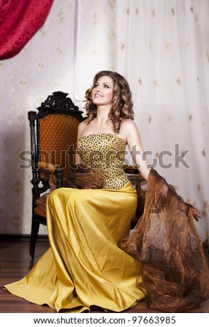 beautiful rich romantic woman in golden dress sitting and smile in luxurious vintage-style retro interior with blond healthy glossy hair. Evening - night. Fashion style shot