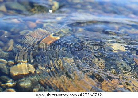 beautiful ripples on river flow over colorful stones in summer sunshine