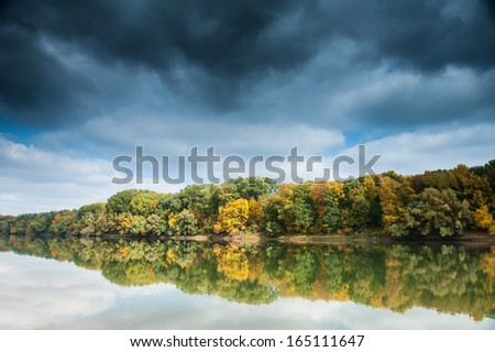 beautiful river and forest with dark sky in autumn