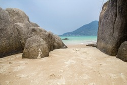 Beautiful rock beach with sea ocean and mountain blue sky landscape background