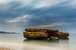 Beautiful rock on the beach of La Galera under a dramatic cloudy sky