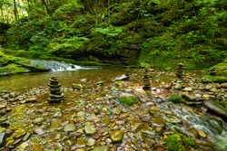 Beautiful rocks formation stacked at sundown forest river cascades