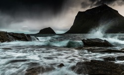 Beautiful rocks on the beach on a moody windy rainy day with a dramatic sky and waves crashing on the beach taken with long exposure which makes the waves silky and moving on lofoten islands in Norway