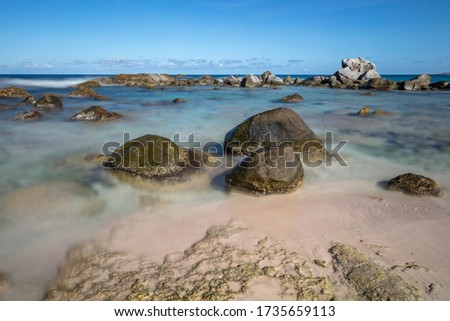 Beautiful rocky beach in Aruba. Three big stones in the foreground. Waves, sky and clouds in the background. Long exposure. Сток-фото ©