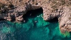 Beautiful rocky beach with SUP stand up paddle boards and with turquoise water in Montenegro. View from above with drone