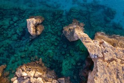 Beautiful rocky coast of Cyprus. Transparent seabed and natural arch. Bridge lovers. View from above