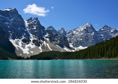 Beautiful Rocky Mountain Peaks Towering Over Evergreen Forest and Teal Lake #286826030