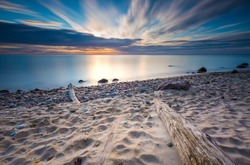Beautiful rocky sea shore with driftwood trees trunks at sunrise or sunset. Baltic sea shore