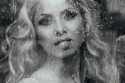 Beautiful romantic blonde bride posing near rainy window face closeup b&w