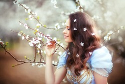 Beautiful romantic brunette girl standing in blooming garden with white flowers on her hair. Smiling and dreaming princess in fairy dress smelling the flowers. Happy day. Fairy tale and fantasy work.