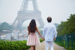 Beautiful romantic couple in love near the Eiffel tower in Paris on a cloudy and foggy rainy day, back view