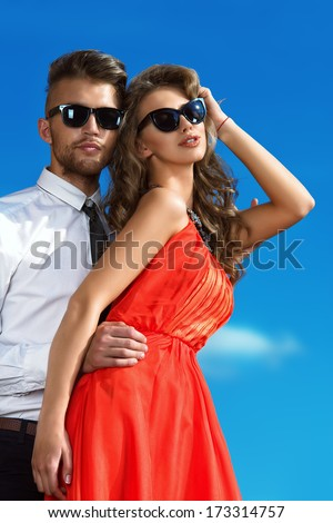 Beautiful romantic couple in love standing over blue sky.