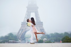 Beautiful romantic couple in love with bunch of white roses having fun near the Eiffel tower on a cloudy and foggy rainy day. Paris, France