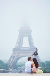 Beautiful romantic couple in love with bunch of white roses sitting and kissing near the Eiffel tower on a cloudy and foggy rainy day, bird is flying over them. Paris, France