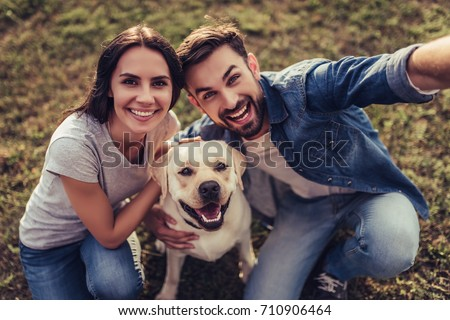 Beautiful romantic couple is having fun with their dog labrador retriever outdoors. Sitting on a green grass and making selfie.