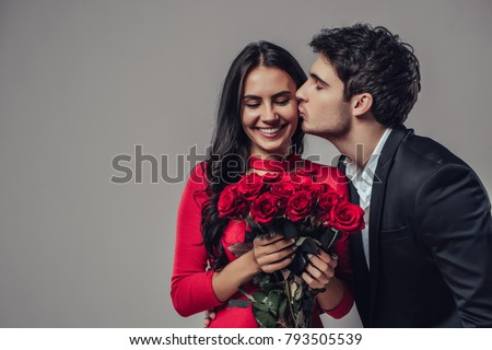 Beautiful romantic couple isolated on grey background. Attractive young woman in dress holding red roses and handsome man in suit are in love. Happy Saint Valentine's Day!