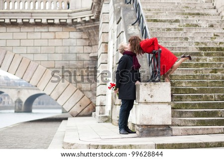 Beautiful romantic couple kissing on a Parisian embankment at spring or winter