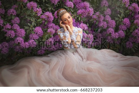 Stock Photo Beautiful Romantic Girl in fairy long lacy dress sitting near pink peonies.Gorgeous young model with perfect hair style and wreath accessories dreaming with close eyes in spring garden.Fantasy art