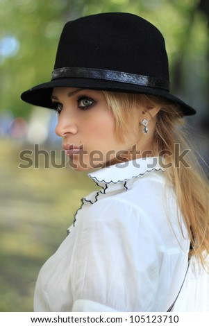 Beautiful romantic girl in the hat in the autumn street