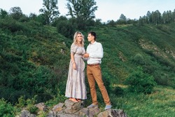 Beautiful romantic inloved couple standing on rocks by the river.