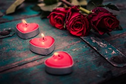 Beautiful romantic red candles with red rose on rustic wooden background