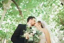 Beautiful romantic wedding couple of newlyweds hugging in green park