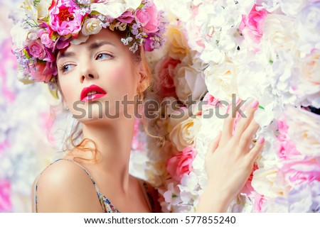 Beautiful romantic young woman in a wreath of flowers posing on a background of roses. Inspiration of spring and summer. Perfume, cosmetics concept.