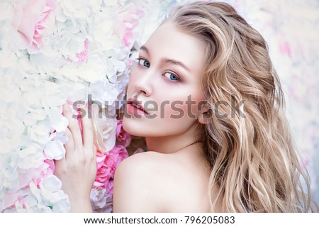Beautiful romantic young woman with natural makeup posing on a background of roses. Perfume, cosmetics concept. #796205083