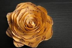 Beautiful rose made of music notes on wooden table closeup