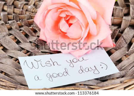 Beautiful rose on wicker mat with card close-up