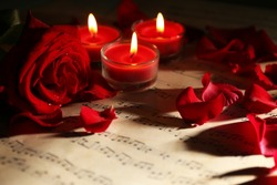 Beautiful rose petals with candles on music sheets, closeup