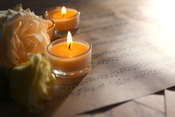 Beautiful rose with candles on music sheets, closeup