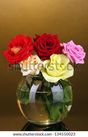 Beautiful roses in glass vase on orange background