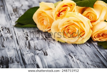 Beautiful roses on wooden dark background